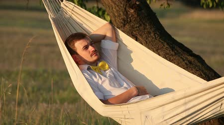 гамак : Young man swinging on hammock at sunset