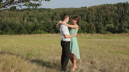 romantic couple : Young couple hugging on the yellow grass Stock Footage