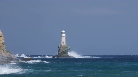világítótorony : Lighthouse on the rock in stormy sea under waves