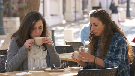 adolescentes : Teenage girls sitting in a cafe, drinking coffee and eating a cake