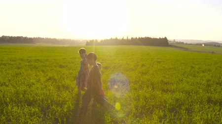 луг : Tracking shot of three kids walking in a field during sunset