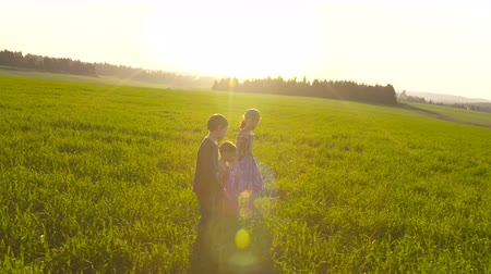 otlak : Tracking shot of three kids walking in a field during sunset