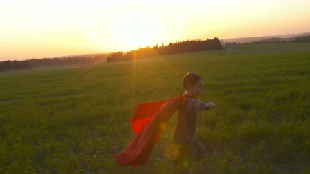 kahraman : Boy dressed in a superhero cape in a field during sunset