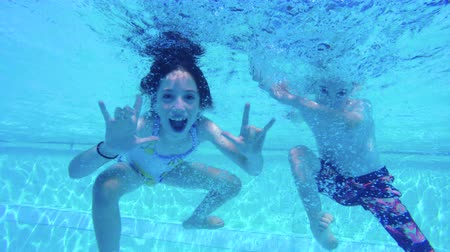 basen : underwater shot of two kids playing and swimming in a pool Wideo