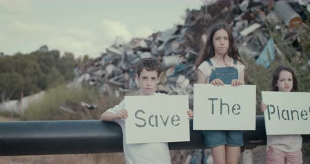 salva vidas : Save the planet. young kids holding signs standing in a large junkyard