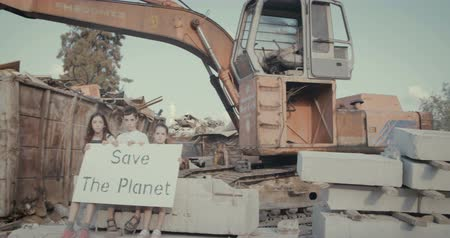 salva vidas : Save the planet. young kids with signs standing in a junkyard