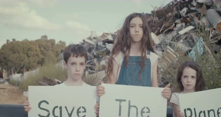 sembol : Save the planet. young kids holding signs standing inside a huge junkyard