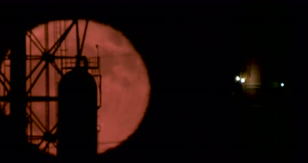 лунный : Red full moon rising from behind a large oil refinery
