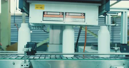 bottling plant : Machines in an automated chemical bottles production line Stock Footage