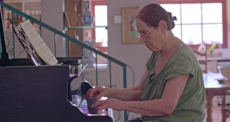 teclas de piano : Anciana tocando un piano de cola en su casa Archivo de Video