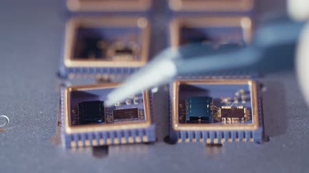 microelectronic : Macro shot of wire bonder connecting wires to a microchip at high speed