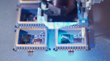 lézer : Macro shot of wire bonder connecting wires to a microchip at high speed
