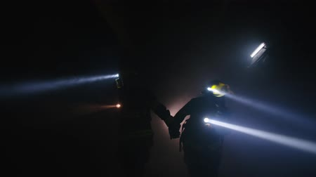 rescuer : Firefighters during a rescue operation in a dark tunnel filled with smoke Stock Footage