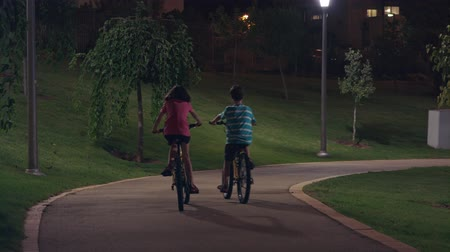 késő : Two kids riding thier bike in a park at night Stock mozgókép