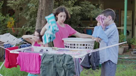 çamaşırhane : Three kids taking off laundry from the hanging line to the basket