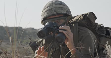 special unit : Israeli soldier crawling from cover and looking through binoculars Stock Footage