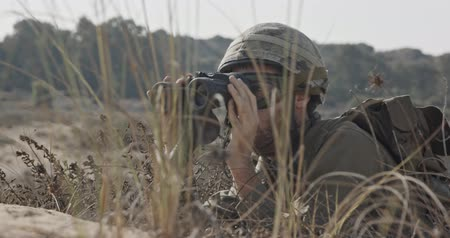 войска : Israeli soldier crawling from cover and looking through binoculars Стоковые видеозаписи