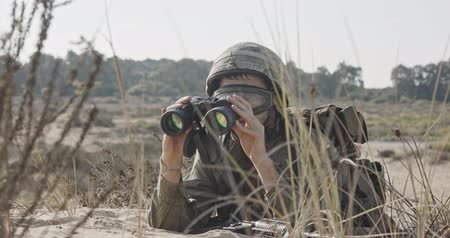 idf : Israeli soldier crawling from cover and looking through binoculars Stock Footage