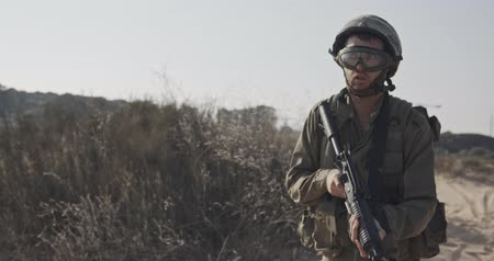 idf : Slow motion of an israeli soldier walking with a rifle on a sand hill Stock Footage
