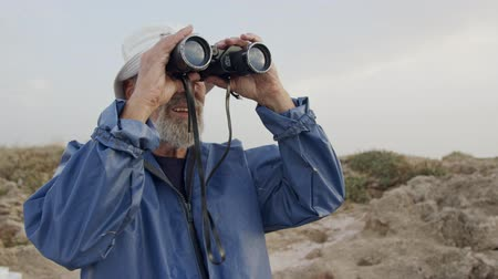fisher : Old fisherman looking into the ocean using his binoculars