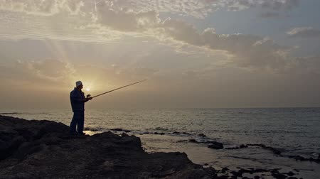 ação : Old fisherman standing on sea side rocks and fishing against the sunset