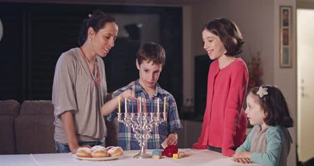 judaizm : Kids and their mother lighting Hanukka candles