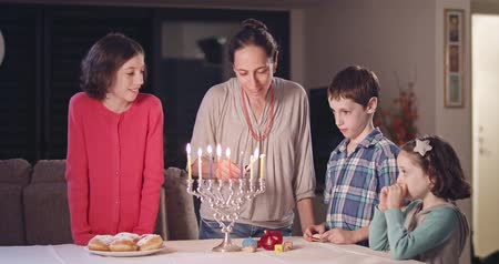 menorah : Kids and their mother lighting Hanukka candles