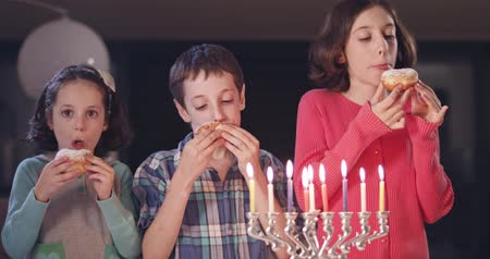 menorah : Kids and their mother eating donuts with a menora and dreidels