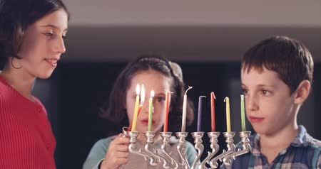 menorah : Children lighting Hanukka candles at home