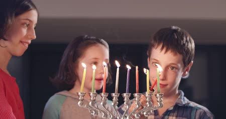 świecznik : Children lighting Hanukka candles at home