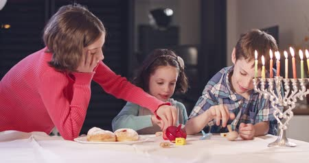 menorah : Kids playing with dreidels during Hanukka at home