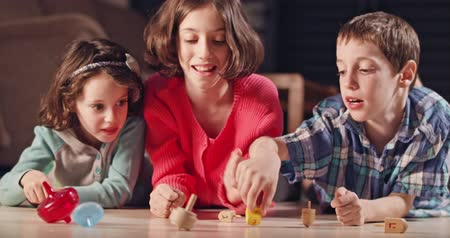 judaizm : Kids playing with dreidels during Hanukka at home