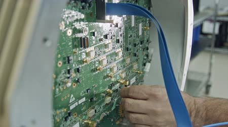 полупроводник : Close up on worker hand connecting wires to a large circuit board Стоковые видеозаписи
