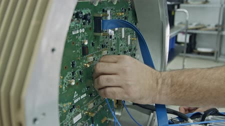 ellenállás : Close up on worker hand connecting wires to a large circuit board Stock mozgókép