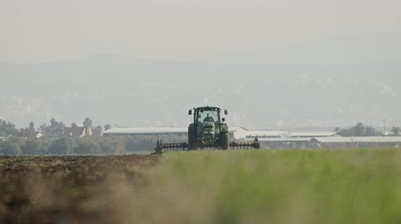 plowed land : Tractor cultivating a green field in slow motion.