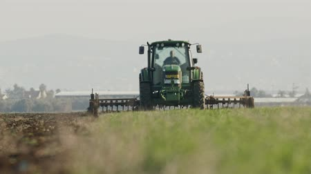 sow : Tractor cultivating a green field in slow motion.