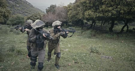 idf : Squad of fully armed commando soldiers during combat in a forest scenery