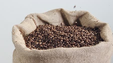 çuval bezi : slow motion of coffee beans falling into a burlap sack