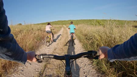POV of two kids enjoying a bicycle ride on the countryside with their father Wideo