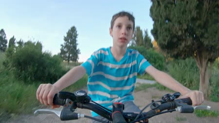 POV of a young boy enjoying a bicycle ride on the rural countryside