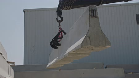 reinforced : Crane lifting a part of a concrete wall at a construction site Stock Footage