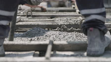 betoniarka : Workers pouring concrete into large steel molds on a construction site Wideo