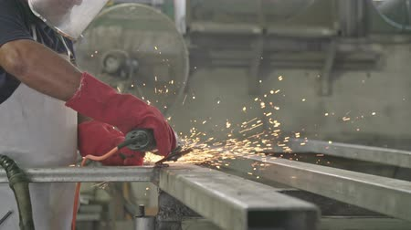 kaynakçı : Slow motion of a worker using metal grinder with sparks flying at a metal shop