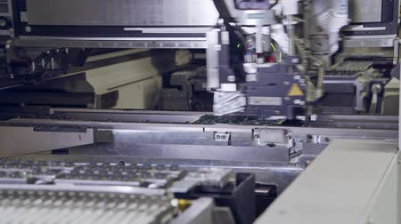 mikroişlemci : Automated SMT machine placing electronic components on a board.