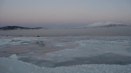 polar circle : Blue sea ice, thick ice fog, snowy mountain and moon in winter