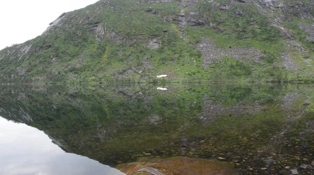 kaperdalen : reflective mountain lake surface and mountain in summer