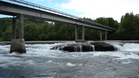 waterfall cascading into pool : massive concrete bridge raging over massive flooded river torrent in summer