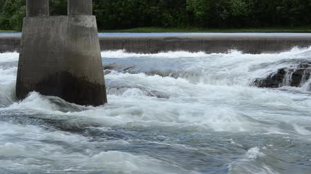 waterfall cascading into pool : massive flooded river stream raging aroung light brown bridge pillar in summer with concrete water barrier in the background Stock Footage