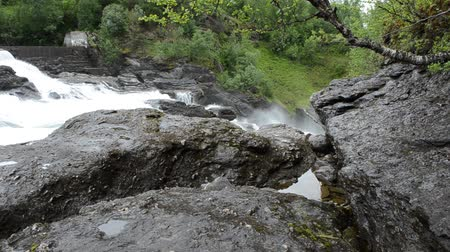 waterfall cascading into pool : beautiful white waterfall in background with wet rocks and stones in the front Stock Footage