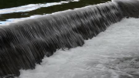 waterfall cascading into pool : clean fast flowing river water flowing over small concrete barrier creating beautiful small waterfall